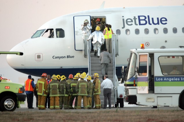 Emergency workers board JetBlue flight 292 as it sits on the runway after making an emergency landing. (Photo by Jeff Gross/Getty Images)