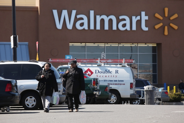 Shoppers exit a Walmart store. (Photo via Getty Images)