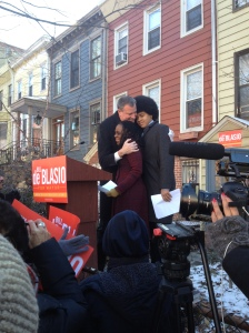 Bill de Blasio hugging his wife and son outside his home today.
