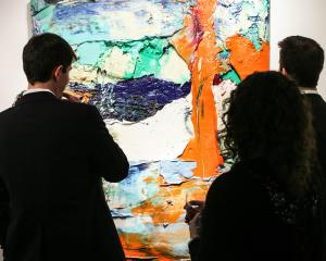 Visitors to the Art Show inspect a painting by Zhu Jinshi. (Courtesy David X Prutting/BFAnyc.com)