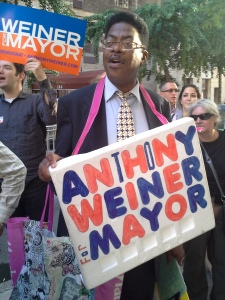 A sign-wielding Anthony Weiner volunteer outside a Hunter College debate yesterday.