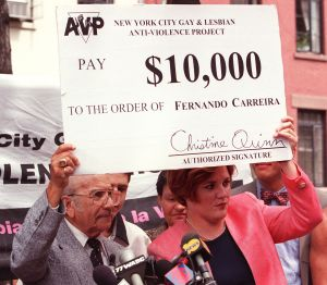 Christine Quinn, executive director of the New York Gay and Lesbian Anti-Violence Project, awards $10,000 to man who helped solve the murder of fashion designer Gianni Versace in 1997. (Photo: Getty)
