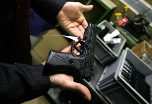 A technician holds a Beretta 92S pistol (Photo: ANDREAS SOLARO/AFP/Getty Images)