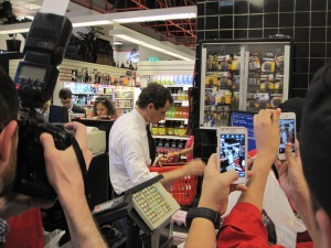 Photographers snap as Weiner pays for his items.