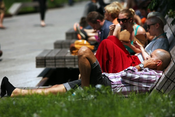 "New Yorkers enjoy the ""slender wooden benches"" at the High Line."