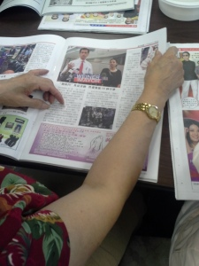 A woman reads about Anthony Weiner's campaign in a Chinese-language newspaper.