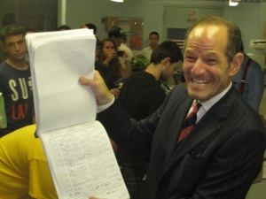 Eliot Spitzer gleefully displays a page of his petition signatures.