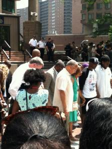 Bill de Blasio, Bill Thompson and others bow their heads in prayer.