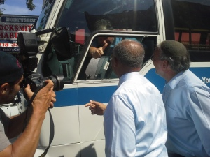 Mr. Thompson and Mr. Hikind greet a bus driver.
