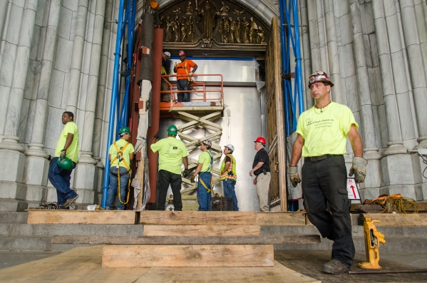 A team of workers supervised the re-installation of the doors. (Fernando Gomes)