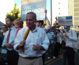 Chuck Schumer campaigns for Daniel Squadron while eating some corn.