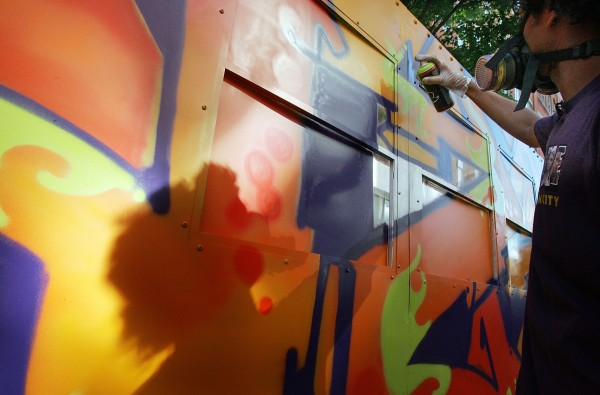 "Graffiti artist Daze paints a mock subway car at Mark Ecko's ""Getting Up"" block party in 2005. (Photo by Mario Tama/Getty Images)"