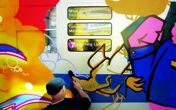 "A graffiti artist spraypaints a mock subway car at Mark Ecko's ""Getting Up"" block party in 2005. (Photo by Mario Tama/Getty Images)"