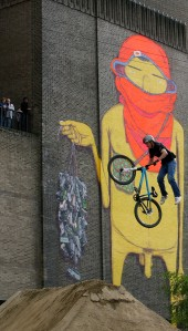 A street biker popping a trick in front of a street-art work by Os Gemeos at Tate Modern. (Photo by Cate Gillon/Getty Images)