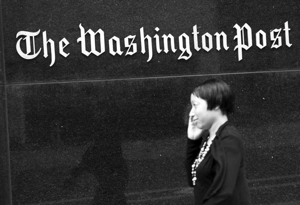 A woman walks past the Washington Post Building August 6, 2013 in Washington, DC, the day after it was announced that Amazon.com founder and CEO Jeff Bezos had agreed to purchase the newspaper.