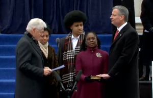 Bill Clinton officiates as Bill de Blasio takes the oath of office next to his family.