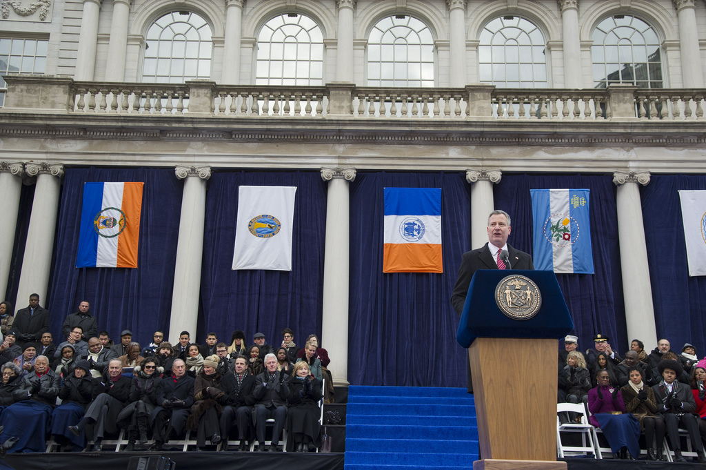 Mayor Bloomberg sitting expressionless in the background as Mayor Bill de Blasio speaks. (Official Photo: New York City Mayor's Office)