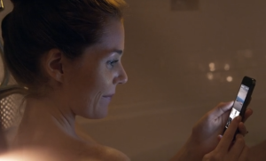 woman checks facebook paper in the tub