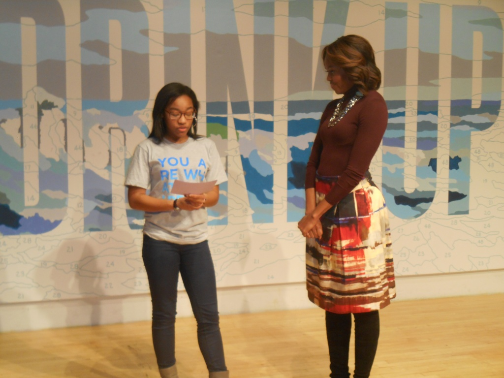 First Lady Michelle Obama speaks with a student at the New Museum today.