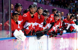 Team Canada players watching the Canada-U.S. semifinal game. (Getty)