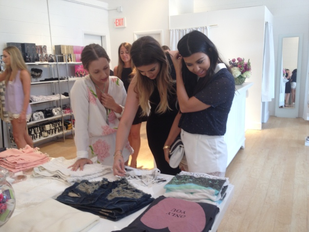 Khloé and Kourtney check out the merchandise (and Jordyn snaps some iPhone photos before a crew member tells her to cut it out). (Photo: Jordyn Taylor)