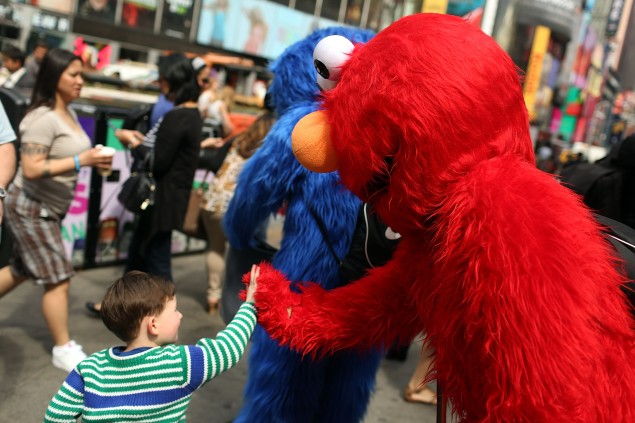 An Elmo costume character greets a child in Times Square. (Photo:Spencer Platt/Getty Images)
