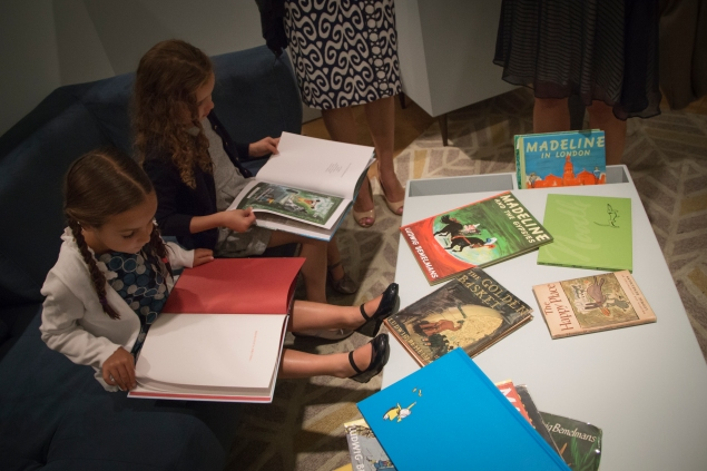 Two girls reading Madeline books on the couch in the exhibit. (Kaitlyn Flannagan)