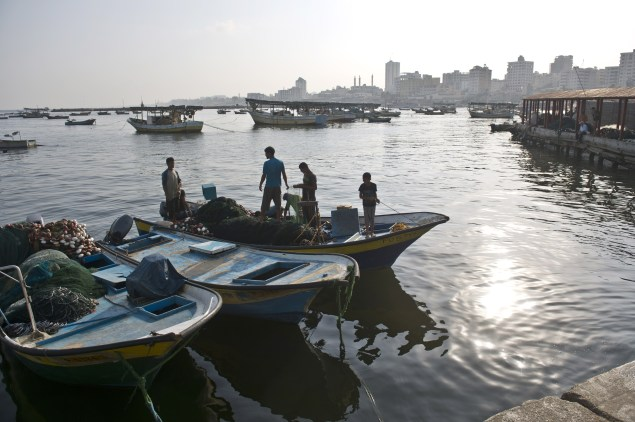 Fishermen stand on a small boat at Gaza City's harbor.  (Photo credit should read ROBERTO SCHMIDT/AFP/Getty Images)