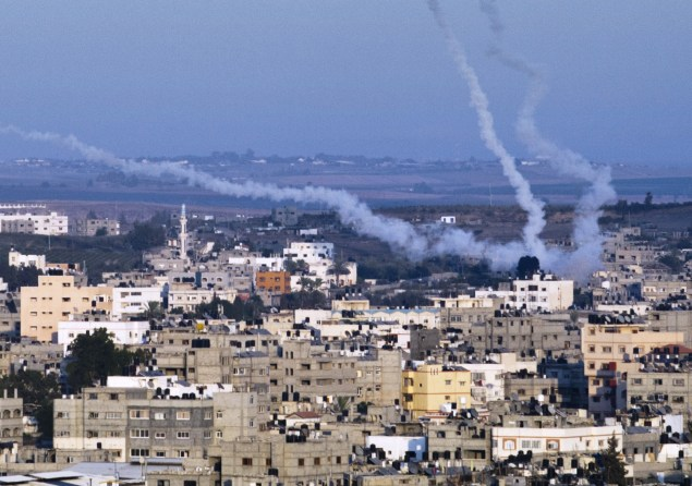 Smoke trails mark the path of Palestinian missiles fired from Gaza City. (Photo by ROBERTO SCHMIDT/AFP/Getty Images)