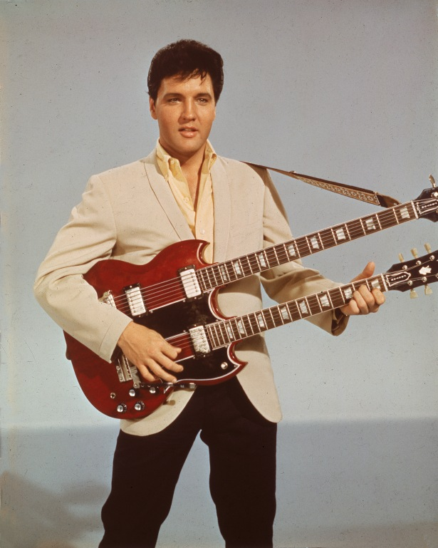 Elvis Presley poses for an iPad picture while holding his iPhone. (Photo via Getty)
