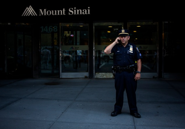 An officer outside Mount Sinai Hospital, where a patient was tested for the Ebola virus. (Photo by Eric Thayer/Getty Images)