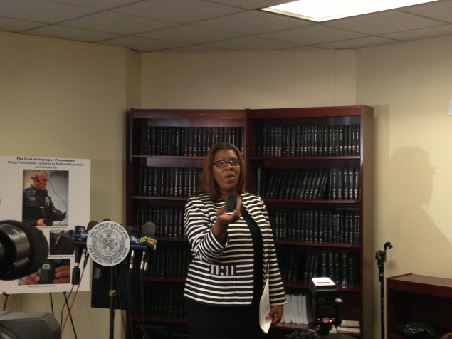 Public Advocate Letitia James holds up an example of a wearable body camera. (Jillian Jorgensen)