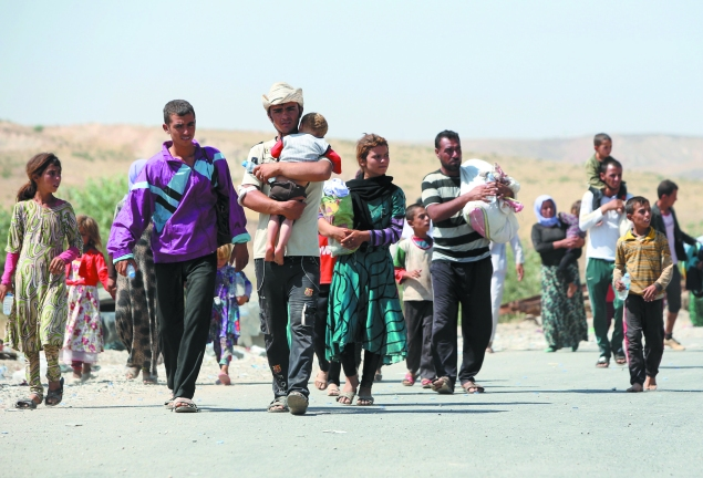 Displaced Iraqis from the Yazidi community carry their children as they cross the Iraqi-Syrian border.
