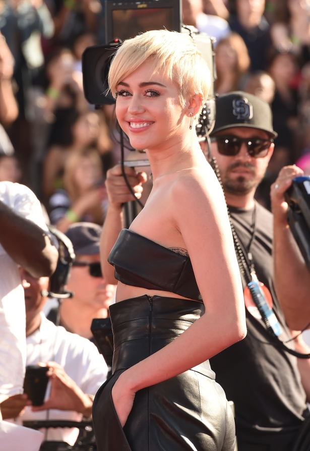Miley reaching for her iPhone (jk) at the VMAs. (Photo via Getty)
