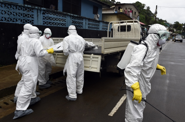 Liberian health workers handle the body of an Ebola victim (cPhoto: Pascal Guyot/AFP/Getty Images).