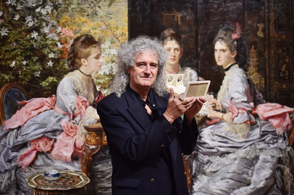 British musician Brian May poses with an owl viewer in front of John Everett Millais painting 'Hearts are Trumps' in 1872 which was inspired by Michael Burr stereoscopic photograph also entitled 'Hearts are Trumps' 1866 as part of an exhibition entitled 'Poor man's picture gallery' : Victorian Art and Stereoscopic Photography at the Tate Britain in central London on October 20, 2014. (Photo by Ben Stansall/AFP, courtesy Getty Images)