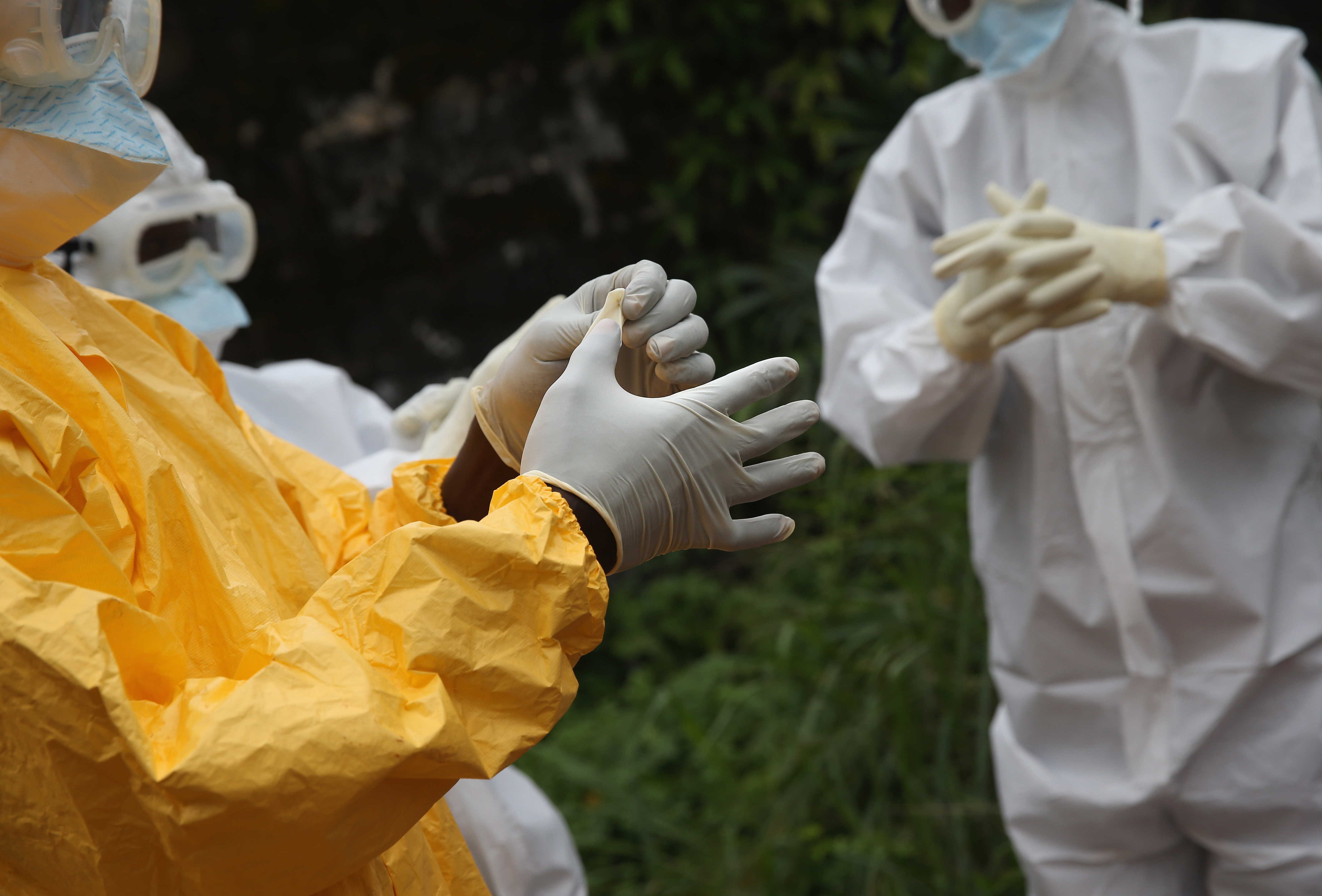 Health workers dress in protective clothing before touching the body of an Ebola victim in Liberia. (Photo by John Moore/Getty Images)