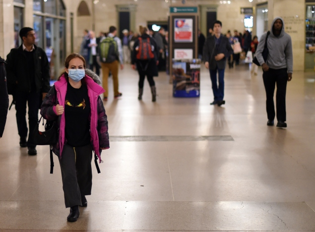A woman wearing a protective mask walks through Grand Central Terminal on October 24, the day after Ebola arrived in New York. (Photo: TIMOTHY A. CLARY/AFP/Getty Images)
