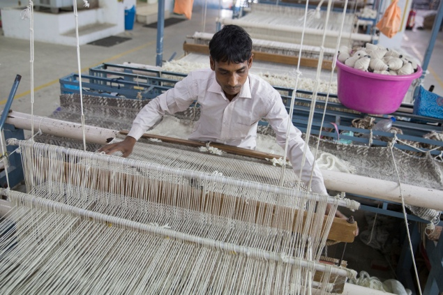Munir Ahmad works at Raj Overseas, West Elm's Indian supplier of Fair Trade rugs, in the first-ever Fair Trade rug factory (photograph by Theodore Kaye © 2014 Fair Trade USA)