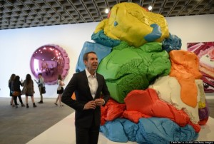 """Artist Jeff Koons poses next to his sculpture  """"Play-Doh"""" during a  preview of """"Jeff Koons: A Retrospective"""" a exhibition of his work at the Whitney Museum of American Art."""