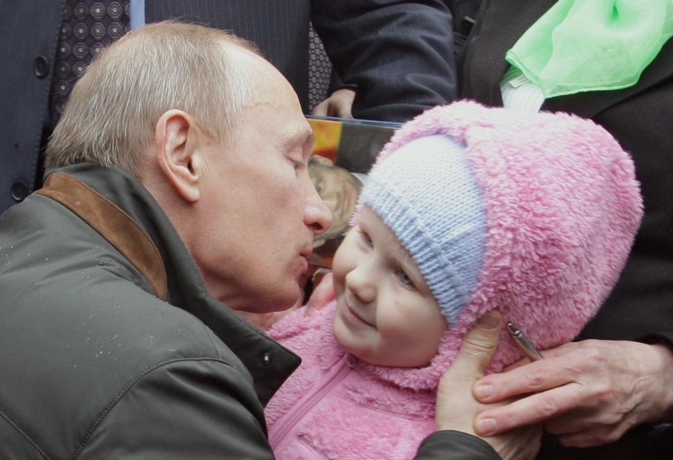 Russian  Prime Minister Vladimir Putin kisses a baby during a visit near St. Petersburg. (ALEXEY DRUZHININ/AFP/Getty Images)