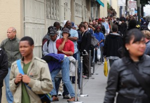 People waiting in line for a free meal in San Francisco's Tenderloin district.  (Photo by Justin Sullivan/Getty Images)