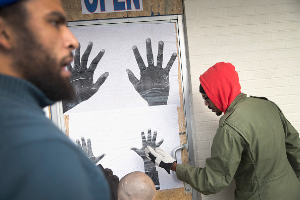 "Damon Davis installs photographs turned into broadsides for his ""All Hands on Deck"" project in Ferguson, Missouri in response to the killing of Michael Brown. (Photo by Scott Olson/ Staff, courtesy Getty Images)"