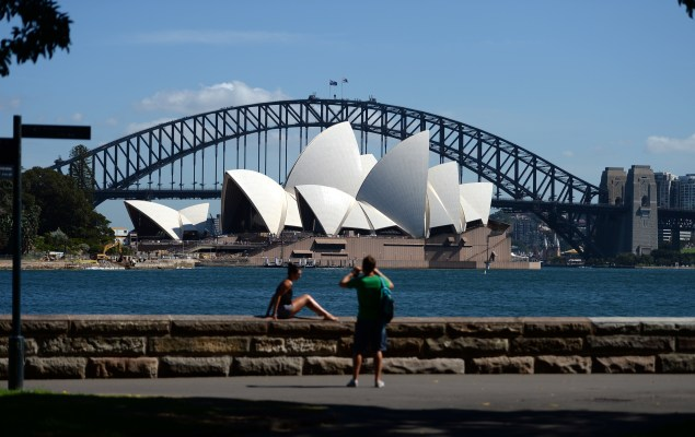 Visitors takes pictures in front of Sydney's iconic landmarks, the Opera House and Harbour Bridge. (Photo by SAEED KHAN/AFP/Getty Images)