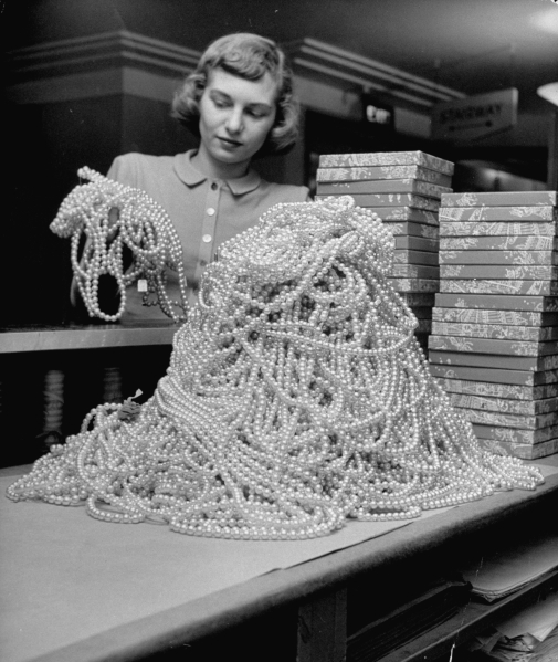 Macy's department store employee Janet Steurer plowing through a pile of costume pearl necklaces. (Photo by Nina Leen/The LIFE Picture Collection/Getty Images)