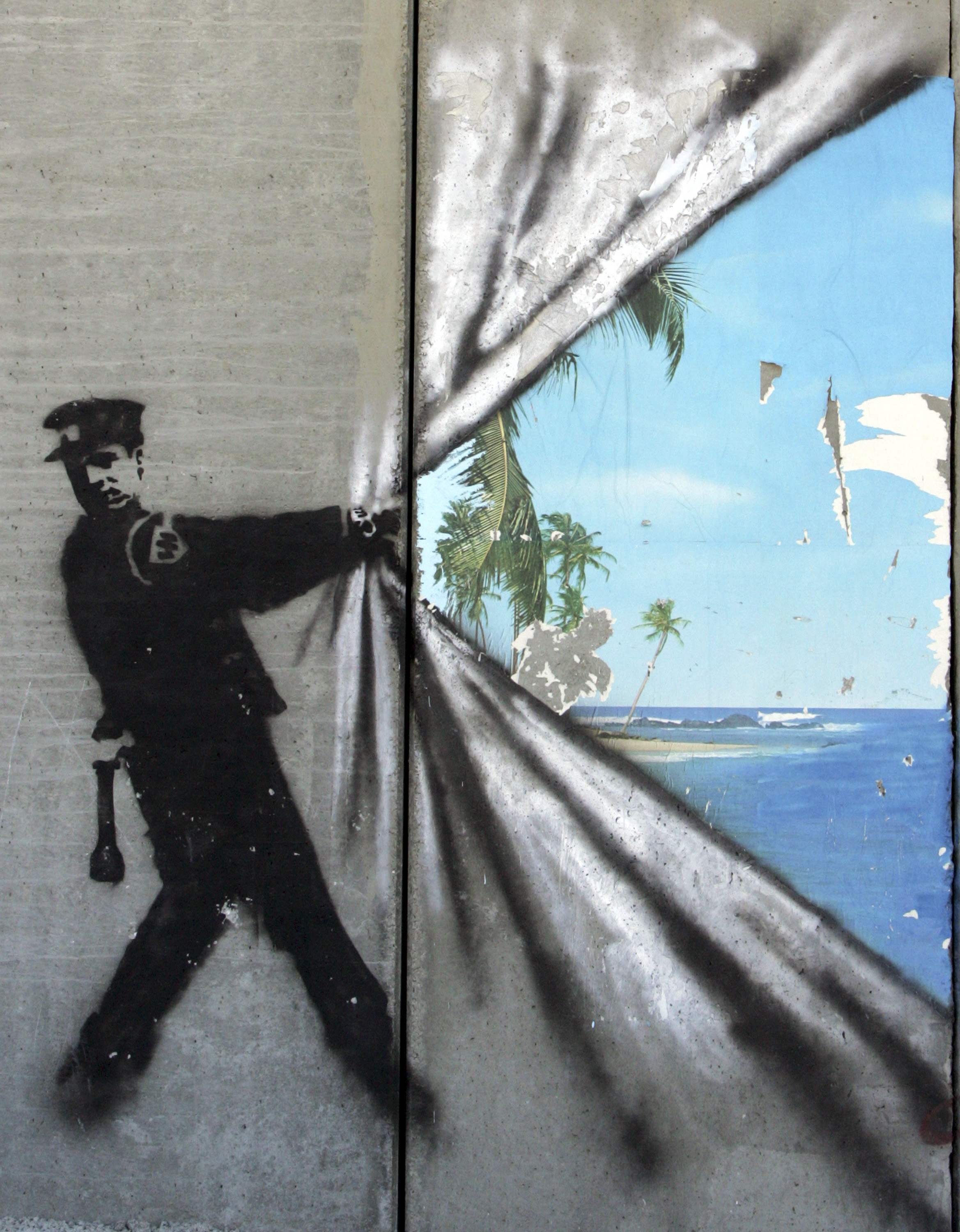 Banksy grafitti enlivens a concrete wall; 'His' works frequently feature or lampoon authoritarian figures.