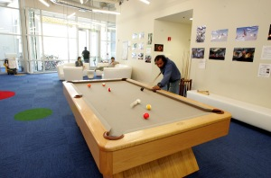 A Google employee plays pool at Google's headquarters.