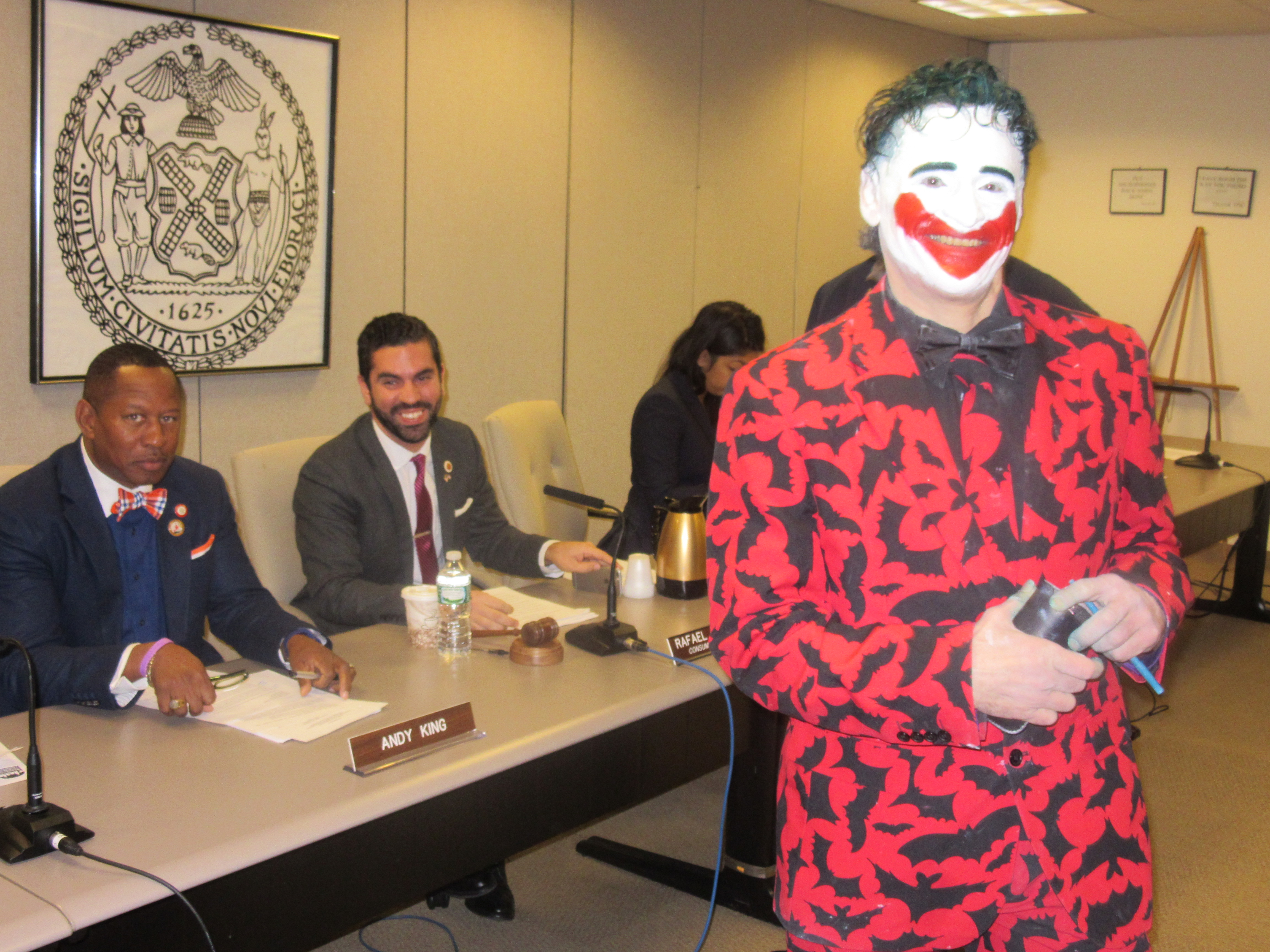 Councilman Andy King and Councilman Rafael Espinal hold their composure as Keith Albahae, also known as the Joker, arrives at the hearing (Photo: Will Bredderman).