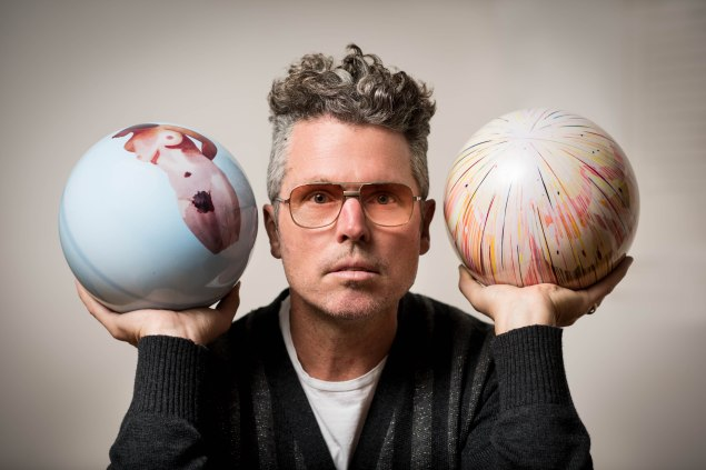 Bill Powers, with bowling balls by Daniel Heidkamp (left) and Jules de Balincourt. (Photo by Francesco Sapienza for The New York Observer)