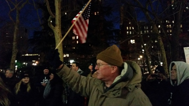 A supporter of the NYPD raises an American flag at a rally tonight. (Photo: Ross Barkan)